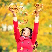 Autumn / fall woman happy throwing leaves up in the air with arms raised up towards the sky with smiling cheerful, elated expression of happiness. Beautiful girl in colorful forest foliage outdoor.