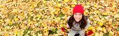 Autumn / fall banner background texture of leaves with happy woman. Panoramic fall concept portrait