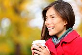 Young woman drinking coffee in Autumn. Fall woman outdoors in autumn forest foliage enjoying hot coffee or tea from disposable mug. Beautiful young female model, mixed race Asian Chinese / Caucasian.