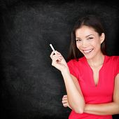 Teacher woman holding chalk by blackboard smiling happy. Young female teaching showing empty blank chalkboard with copy space for text. Young female Asian Caucasian teacher or student in her 20s.