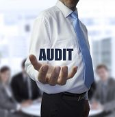 Elegant businessman holding the word audit in front of a business team