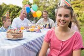 Little girl smiling at camera at her birthday party outside at picnic table