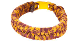 stock photo of paracord  - Paracord survival Bracelet using a In and Out weave in yellow and rust colored cord - JPG