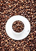 White Coffee Cup With Saucer Full Of Roasted Coffee Beans On Coffee Beans Background. Coffee Backgro