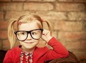 pic of comedy  - Funny little girl with glasses on brick wall background - JPG