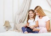Mother Reading Bed Time Story Book To Her Daughter