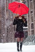 Woman With Umbrella Enjoy Snowfall On Street