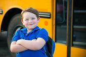 image of knapsack  - Happy young boy in front of school bus going back to school - JPG