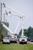 stock photo of utility pole  - Utility Workers working on electrical cables on utility poles - JPG
