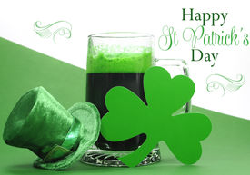 stock photo of stein  - Happy St Patricks Day green beer in large glass stein with shamrocks and leprechaun hat and sample text greeting on green and white background - JPG