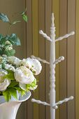 Close Up Flower And White Wooden Standing Cloth Rack Behind