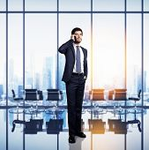 Businessman standing in bright modern office with large windows