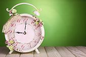 Beautiful vintage alarm clock with flowers on wooden table, on green background