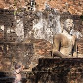 SUKHOTAI,THAILAND - FEBRUARY 4, 2013: Tourists making picture in Sukhotai Historical Park. Sukhothai is the capital of Sukhothai kingdom in the 13th and 14th centuries