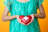 Red heart with cross sign in female hand, close-up, on color background