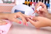 stock photo of finger-painting  - Young woman is getting manicure in beauty salon - JPG