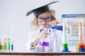 Curious schoolgirl pouring reagent into flask