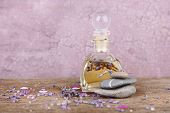 Spa still life with lavender oil and flowers on wooden table, on pink background