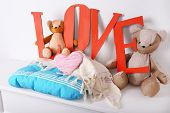 Decorative letters forming word LOVE with teddy bear on wall background