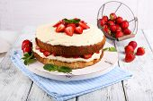 Delicious biscuit cake with strawberries on table on light background
