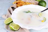 Tasty soup with oysters on wooden table