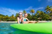 Mother and her adorable little daughter paddling on stand up board having fun during summer beach va