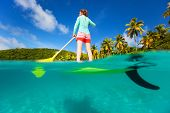 Split underwater photo of active young woman on tropical beach vacation paddling on stand up board