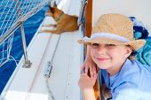 Adorable little girl and her pet dog enjoying sailing on a luxury catamaran or yacht