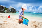 stock photo of coast guard  - Adorable little girl wearing rash guard for sun protection at beach during summer vacation - JPG