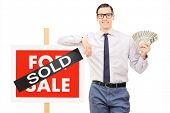 Male realtor holding money next to a sold sign isolated against white background