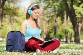 Woman with headphones studying in park seated on the grass