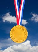 Golden medal in front of blue sky.