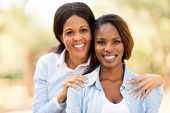 portrait of happy middle aged african mother and adult daughter outdoors
