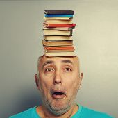 surprised senior man with books in the head over grey background