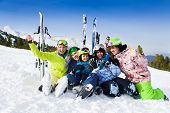 Smiling friends after skiing sitting on snow