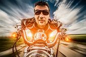 Funny Biker in sunglasses and leather jacket racing on the road with the sun in the background