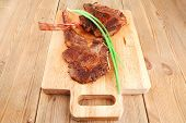 meat savory : grilled beef ribs served with green chives on wooden table