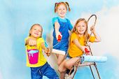 Three little girls smile on a background of wall