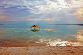 Winter in the Dead Sea. Excellent optical effects and reflections of clouds and sun in the water. Red gazebo in the water near the shore