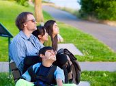 Disabled Boy In Wheelchair With Family Outdoors On Sunny Day Sitting At A Park