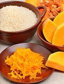 Ripe Raw Pumpkin With Grated Pumpkin And Uncooked Rice On The Brown Plate