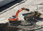 Excavator Loading Dumper Truck Tipper In Sandpit In Highway Construction Site