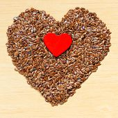 Raw Flax Seeds Linseed Heart Shaped On Wooden Table