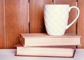 Old books and cup of tea on table