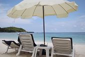 Umbrella, Two Chairs And A Table On The Beach
