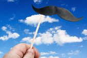 Mustache On A Stick Against The Sky With Clouds