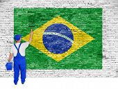 House Painter Covers Brick Wall With Flag Of Brazil
