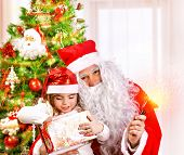 Christmas party for children at home, adorable little girl and old Santa Claus with big white beard open Christmas present, happiness concept