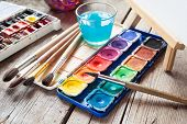 picture of canvas  - Box of watercolor paints art brushes glass of water and easel with canvas or paper on old wooden table - JPG