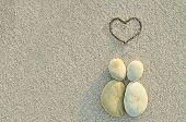 stock photo of lovers  - Pebbles shapes lovers with heart on the sand - JPG